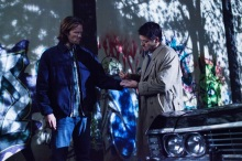 Sam and Castiel, who seems to be drawing a rune on Sam's hand